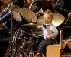Photo of adorable three year old playing the drums.