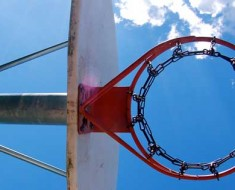 Photograph of a basketball hoop on an outdoor court, looking up towards the sky.